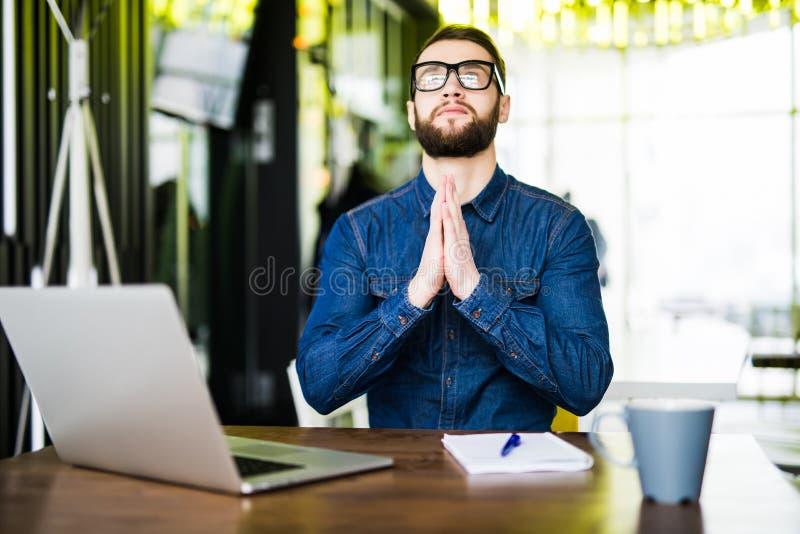 be framgång Främre sikt av fundersamma innehavhänder för ung man på hakan och att se upp, medan sitta på hans arbetsplats in fotografering för bildbyråer