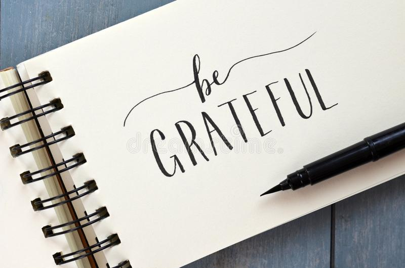 BE GRATEFUL hand-lettered in notepad with brush pen stock photo