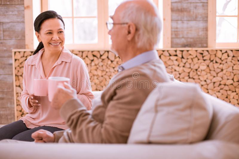 Positive delighted Asian woman having pleasant talk. Be happy. Attentive mature men sitting in semi position and drinking tea royalty free stock images