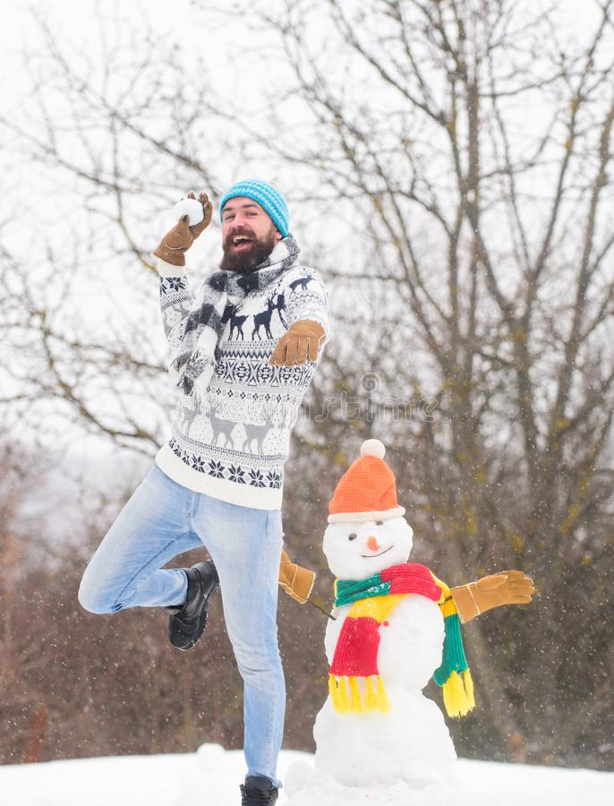 Be happy. happy hipster ready for xmas. winter season. Merry christmas. winter holiday. warm sweater in cold weather. Man having fun. bearded man build snowman stock images