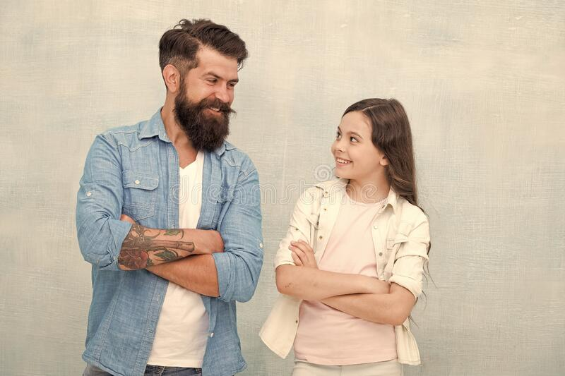 Be happy and smile. Happy family. Happy father and little daughter keeping arms crossed on grey background. Bearded man stock image