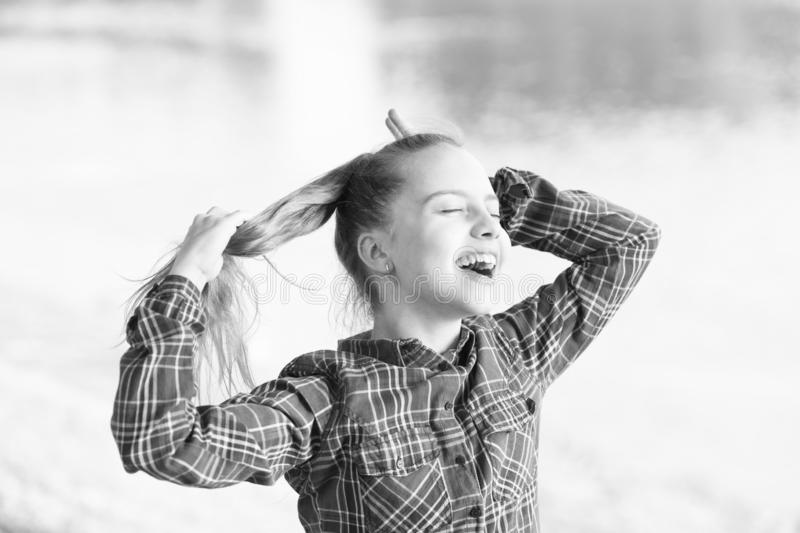 Be happy and smile. Happy little girl enjoy doing her hair on summer day. Adorable small child with long blond hair and stock image