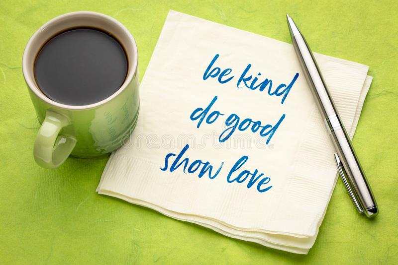 Be kind, do good, show love. Inspirational handwriting on a napkin with a cup of coffee stock image