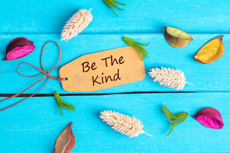 Be the kind text on paper tag. With rope and color dried flowers around on blue wooden background stock photo