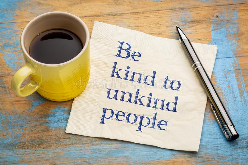 Be kind to unkind people. Inspirational handwriting on a napkin with a cup of espresso coffee stock image