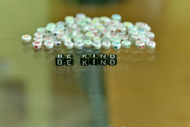 BE KIND  written with Acrylic Black cube with white Alphabet Beads on the Glass Background.  royalty free stock photography