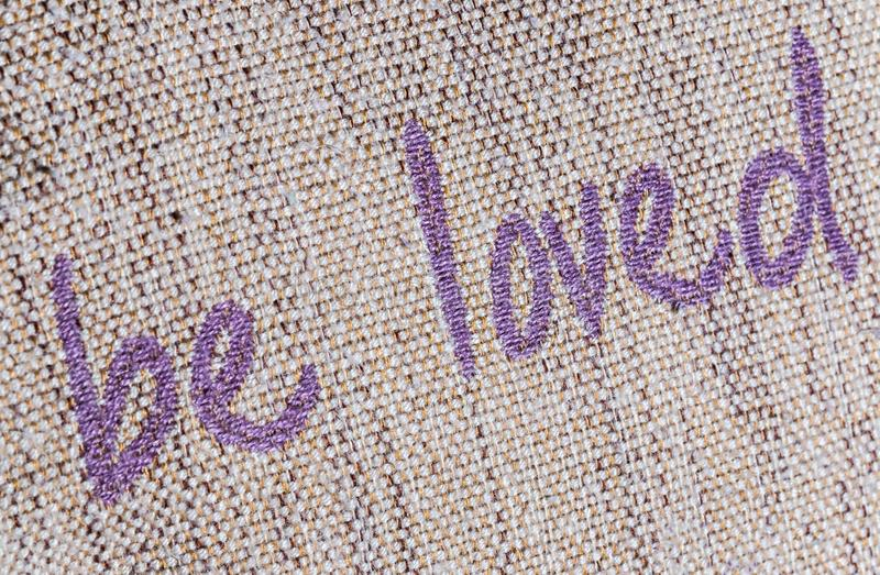 Be Loved Writing Macro. Be loved writing sewn on fabric royalty free stock photo