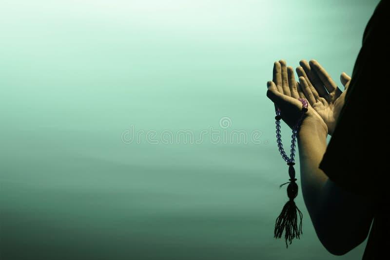 be Lyfta b?da ?ppna armar som dekoreras med b?np?rlor f?r att be till guden Isolerade begreppet av dyrkan av en muselman arkivbilder