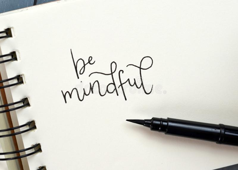 BE MINDFUL hand-lettered in notepad royalty free stock photo