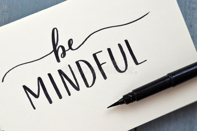 BE MINDFUL hand-lettered in notepad with brush pen royalty free stock image