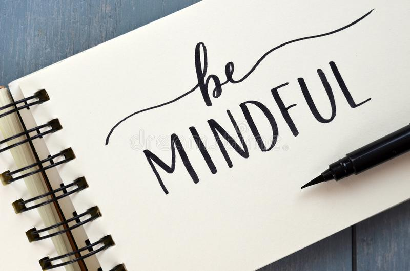 BE MINDFUL hand-lettered in notepad with brush pen stock photography
