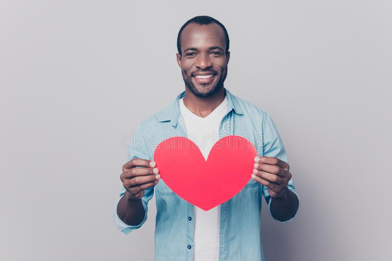 Be my girlfriend! I love you! Portrait of tender gentle romantic. Sweet lovely open-hearted african man showing big red heart in hands isolated on gray stock image