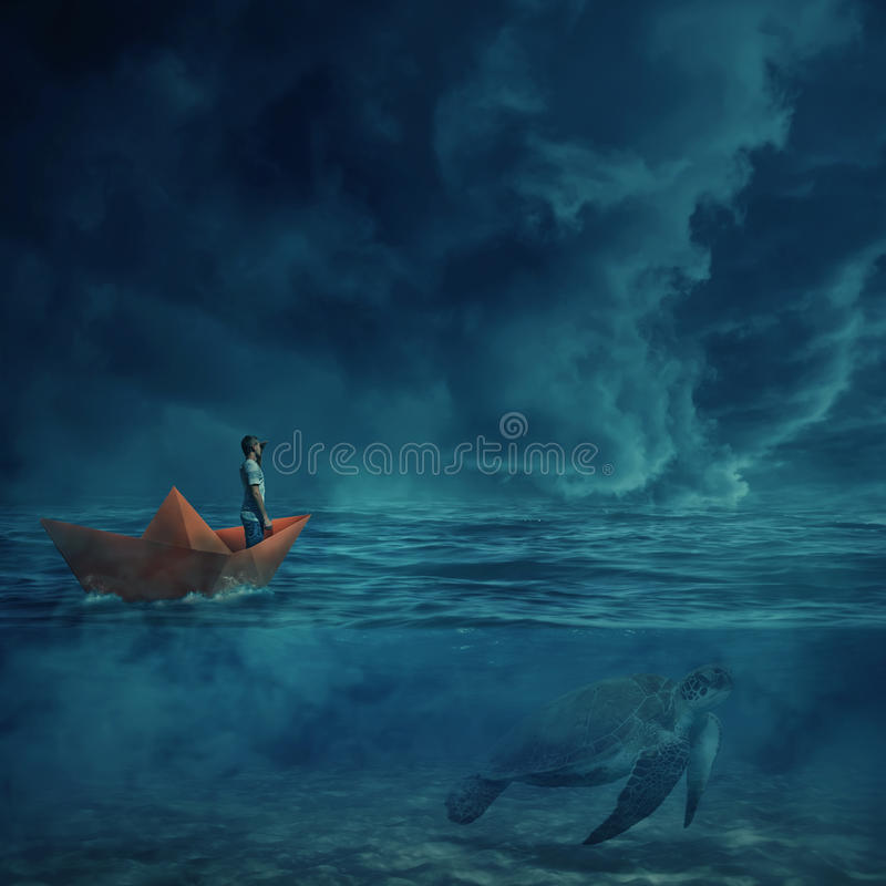 Be my guide. Young boy in a orange paper boat sail lost in the ocean, in a stormy night and a huge turtle underwater, as a guide, show him the way home royalty free stock photography