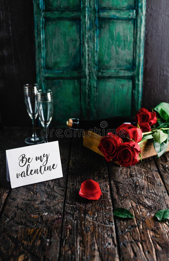 Be my valentine greeting card, red roses and champagne bottle with glasses stock photo