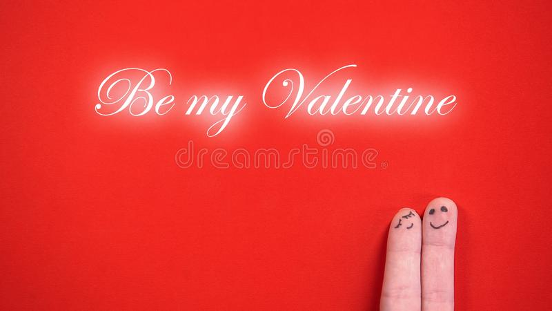 Be my Valentine phrase and hugging finger face pair on red background, concept royalty free stock image