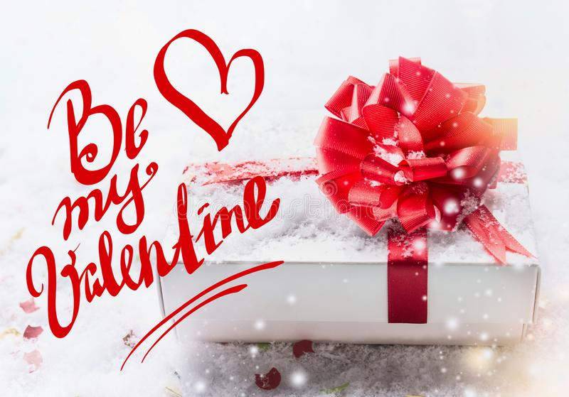 Be my Valentine text lettering with white gift box, red bow on snow with bokeh and snowfall. Valentines day, declaration of love royalty free stock image