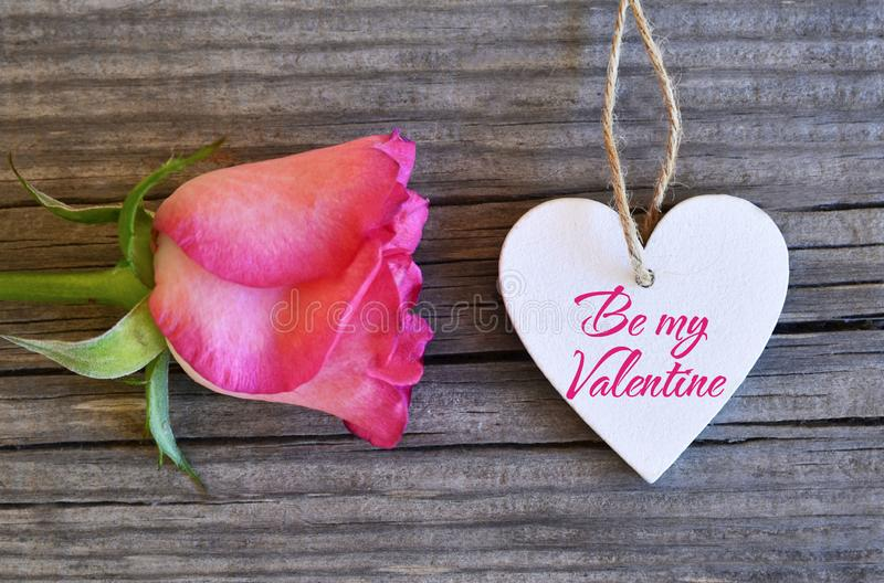 Be my Valentine.Valentines Day greeting card.Rose and decorative white heart on old wooden background.St.Valentine`s Day concept. Selective focus royalty free stock image