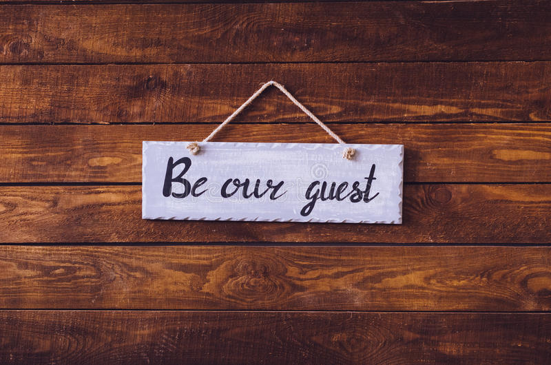 Be our guest. Wording on board hanging on a rustic wooden background. Welcome concept. Toned image stock images