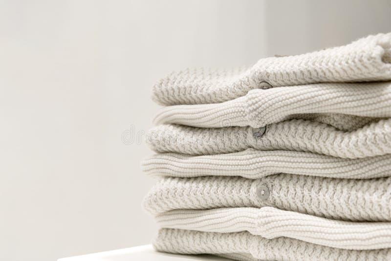 Be?owi pulowery robi? od naturalnych tkanin sk?adaj? na stole zdjęcia stock