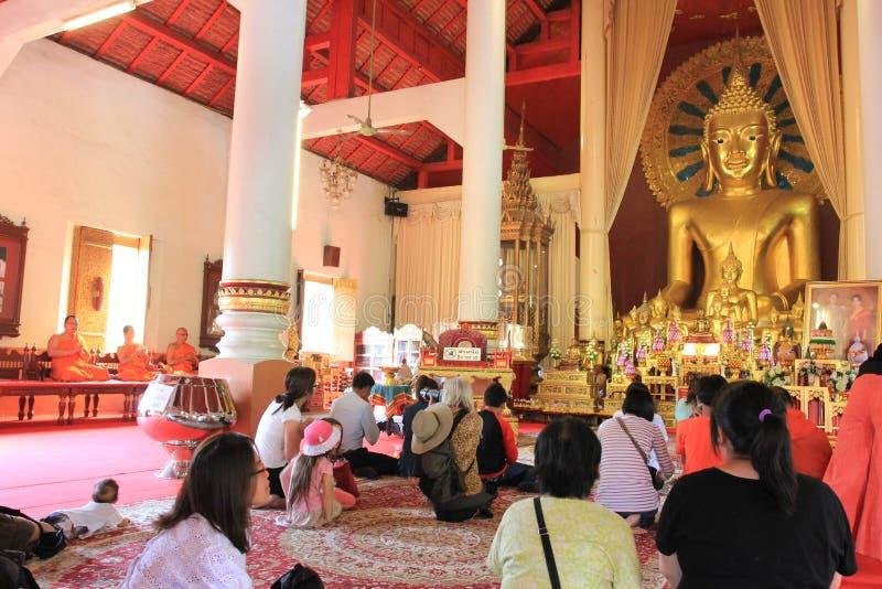 Be på en buddisttempel arkivfoto