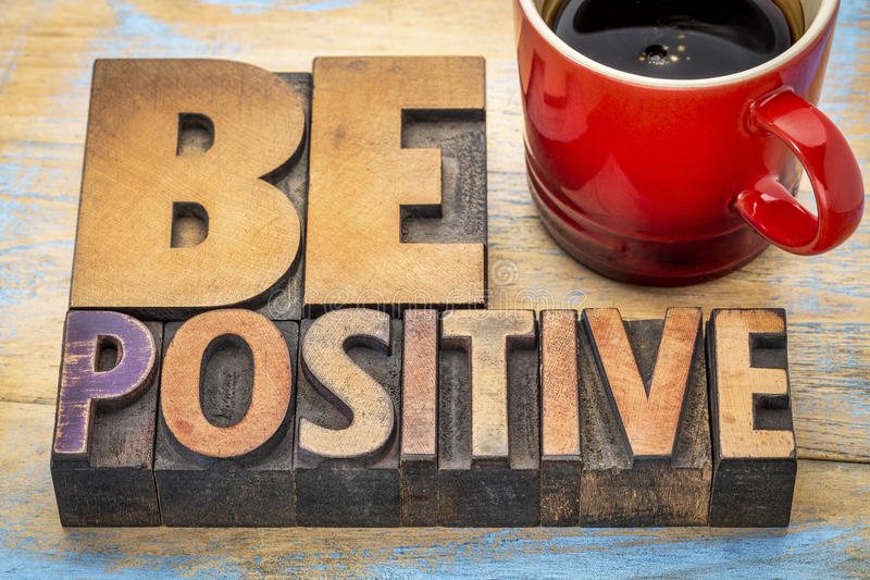 Be positive banner in letterpress wood type. Be positive banner in vintage letterpress wood type blocks stained by color inks with a cup of espresso coffee royalty free stock images