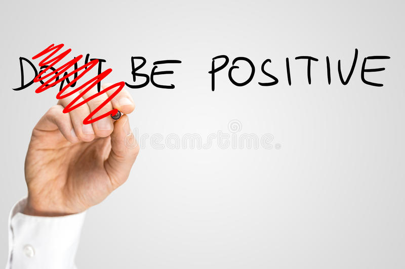 Be positive. Concept of positivity and optimism - male hand changing a Don't be positive into a Be positive sign stock photo