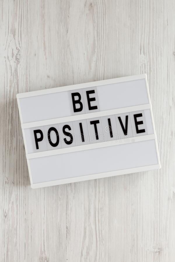 `Be positive` words on a lightbox on a white wooden background, top view. Overhead, from above, flat lay.  royalty free stock photo