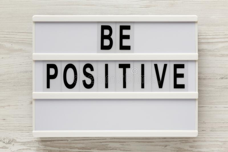 `Be positive` words on a modern board on a white wooden background, top view. Overhead, from above, flat lay. Close-up.  stock photos