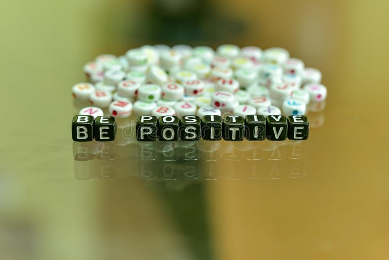 BE POSITIVE  written with Acrylic Black cube with white Alphabet Beads on the Glass Background.  stock photography