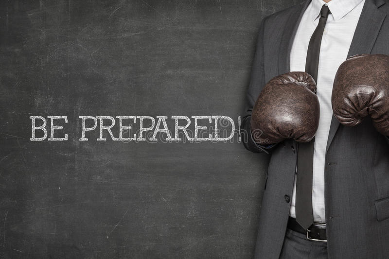Be prepared on blackboard with businessman. Wearing boxing gloves stock photography