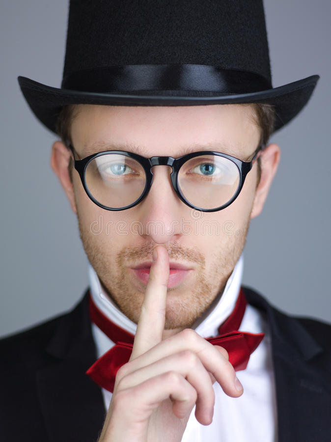 Be quiet. An attractive young man wearing a black top hat and red bow tie holds his finger to his lips to be quiet stock photography