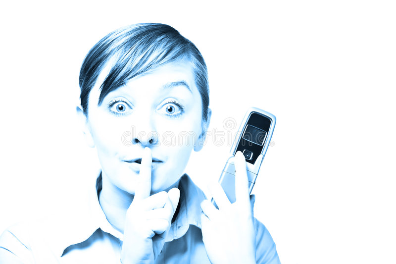 Be quiet. Woman holding mobile phone and holding finger on lips to be quiet. Isolated on white. Blue tone photo royalty free stock photography