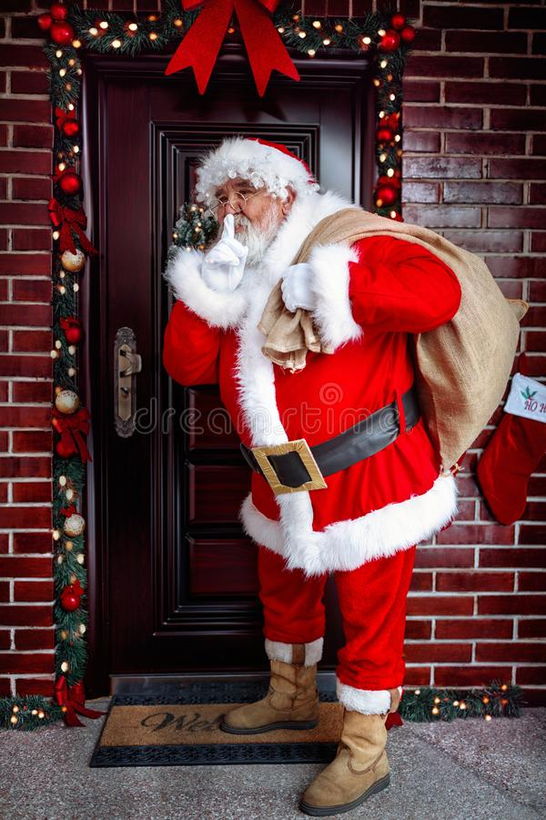 Be Quiet- Santa Claus arrives with the Christmas present. In Christmas night stock photography