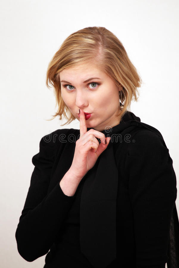 Be quiet sign by girl. Pretty female with finger on lips makes a be quiet gesture stock photography