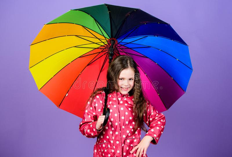 Be rainbow in someones cloud. Rainy day fun. Happy walk under umbrella. Enjoy rain concept. Kid girl happy hold colorful royalty free stock photo