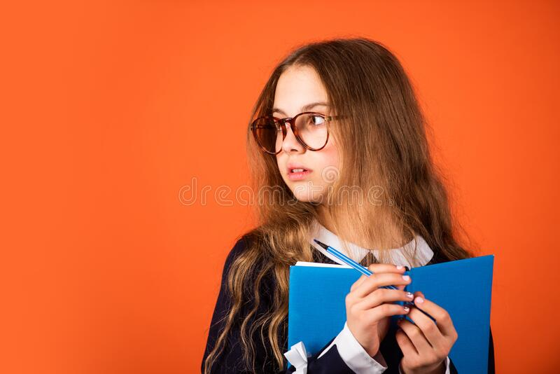 Be smarty. Smart girl brown background. Little girl back to school. Small girl read book in glasses. Primary school girl. With long hair. School and education stock photos