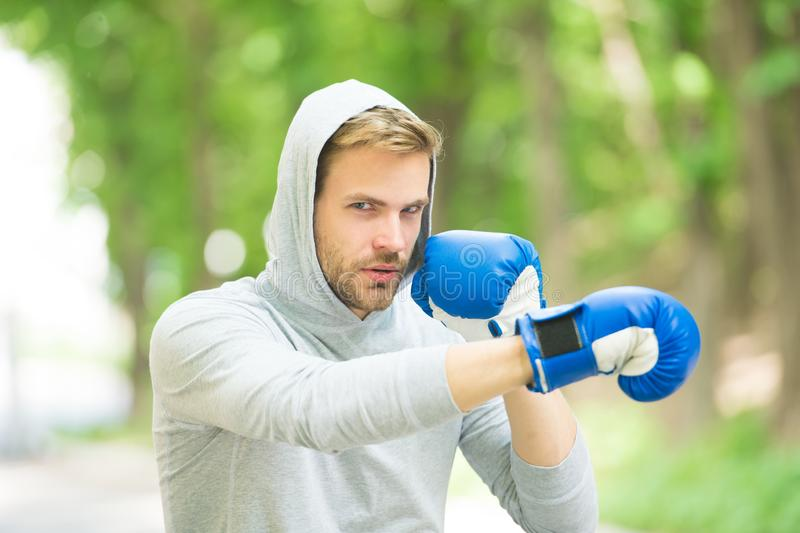 Be strong. man in boxing gloves punching. Sport and sportswear fashion. boxer man in hood. ready to fight. knockout and. Energy. Sport success. Boxing school royalty free stock image