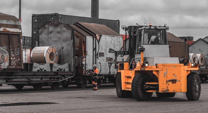 Be- und Entladungs-Ladevorgang von Stahlspulen im Frachthafen Tragen Sie Stahlspulen Hebernehmenspule vom Lastwagen Stevedor über stockfotos
