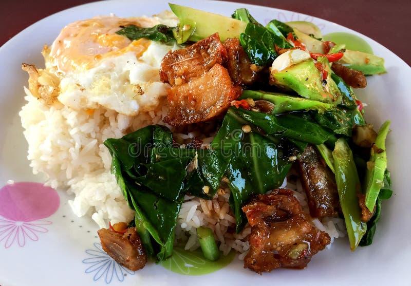 Be*wegen-gebraden Boerenkoolgroente met Knapperig Varkensvlees en Fried Egg Over Rice stock afbeelding