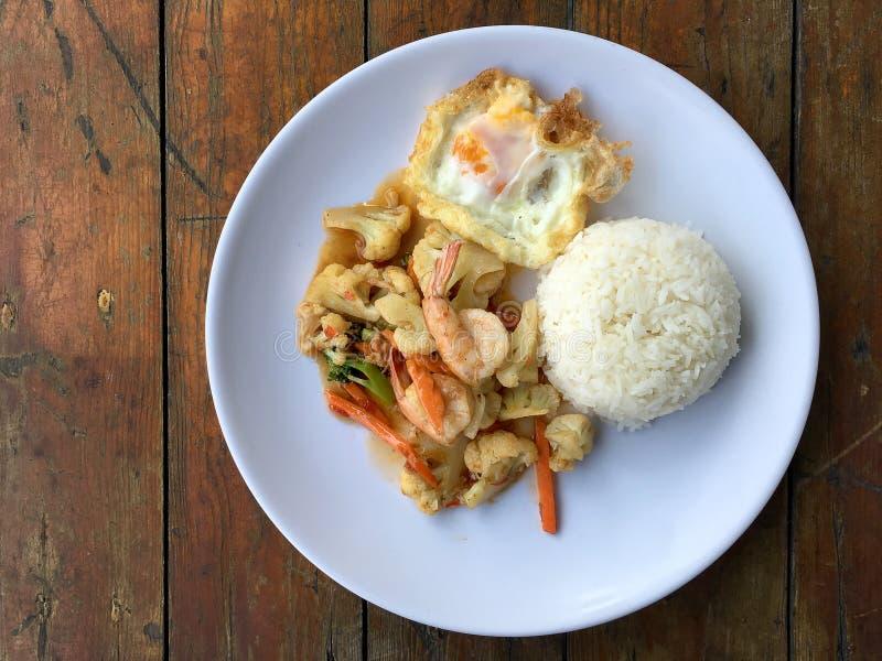 Be*wegen-gebraden gerechtgroenten met tahoe en garnalen in witte schotel met rijst en gebraden ei op houten achtergrond Thais sti stock foto