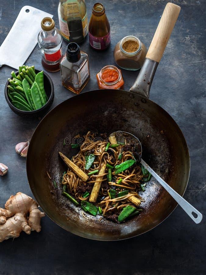 Be*wegen-gebraden rundvlees en noedels met oestersaus in een wok, voorbereidingsproces royalty-vrije stock afbeelding