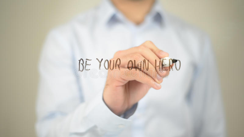 Be Your Own Hero, Man writing on transparent screen royalty free stock photo