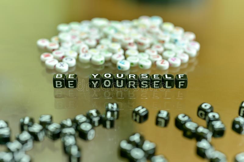 BE  YOURSELF  written with Acrylic Black cube with white Alphabet Beads on the Glass Background.  royalty free stock photos