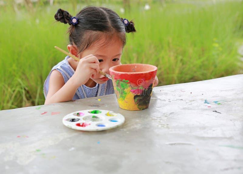 Beabsichtigen Sie asiatische Kinderm?dchenfarbe auf T?pferwarenteller stockbilder