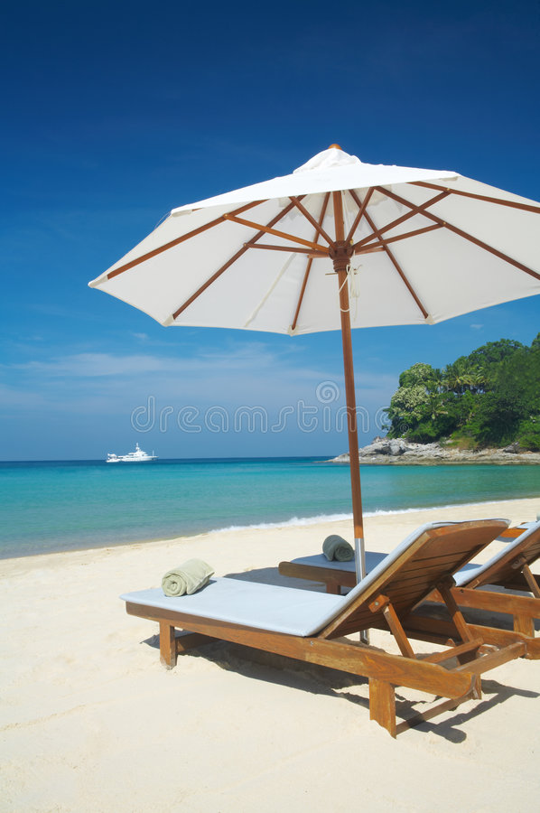 On the beach. View of two chairs and umbrella on the beach