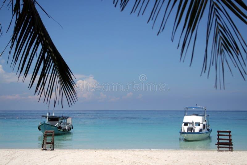 Beach with 2 boats stock photos