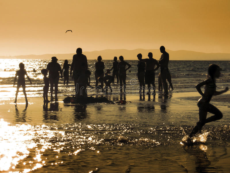 On the beach. Group of various people on the beach on sunset royalty free stock images