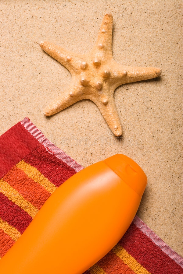 At the beach. One sea star and a bottle of uv protection lotion stock photos