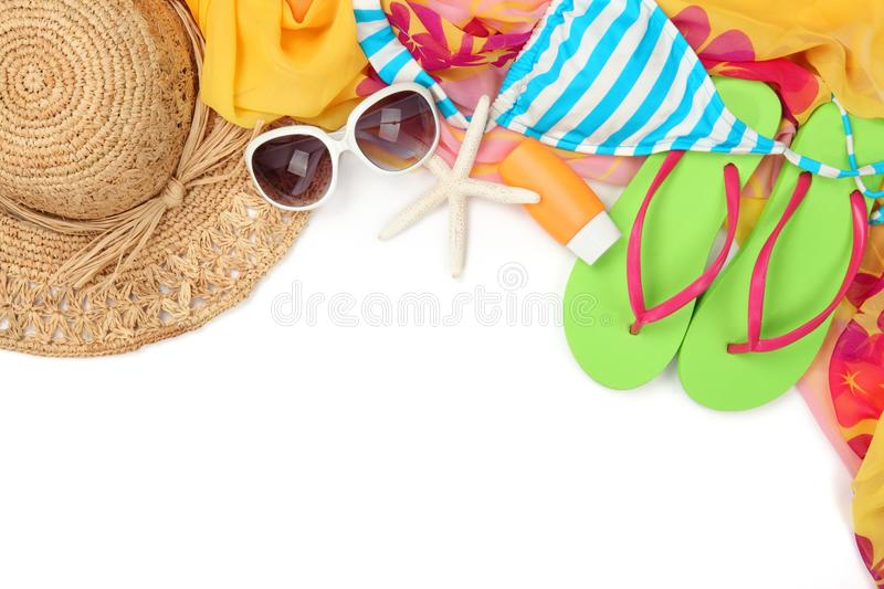 Beach accessories. With straw hat, swimming suit,sun glasses,shawl and flip flops on white background royalty free stock images