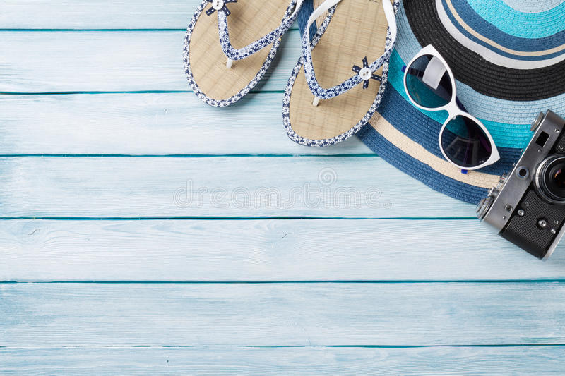 Beach accessories. Flip flops, camera, hat and sunglasses. On wooden background. Top view with copy space royalty free stock photo